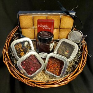 Tea and Hygge gift basket with four tins of tea, honey, cookies, and strainer ball